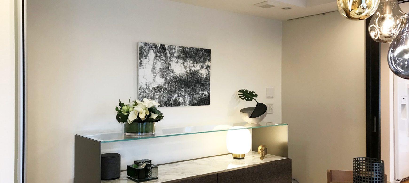 ガラスの棚の上に飾った池田恭子のインテリアアートパネル